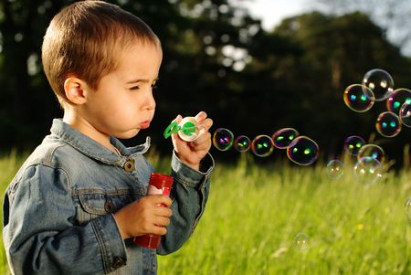 Little boy makes bubbles in the sunset outdoors Stock Photo - 7050601