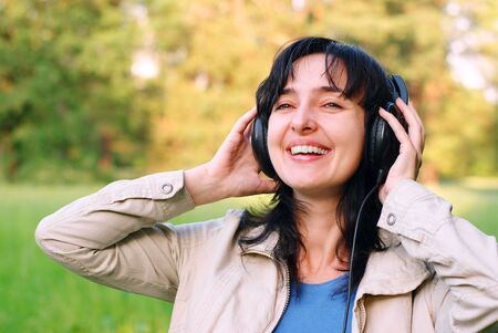 Beautiful brunette woman enjoyes the music in headphones outdoors on the meadow Stock Photo - 7050599