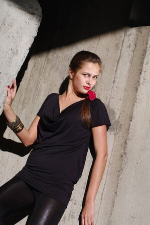 Fashion model lean by the concrete wall glance looking in camera photo