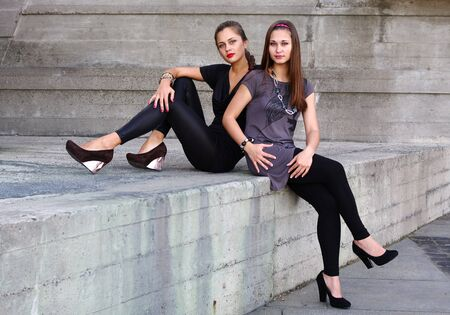Two beautiful girls outdoors sitting on concrete construction photo