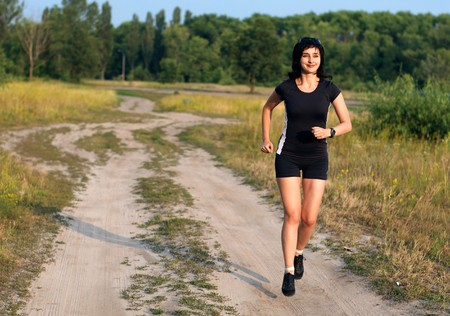 Happy woman jogging outdoors in summer photo