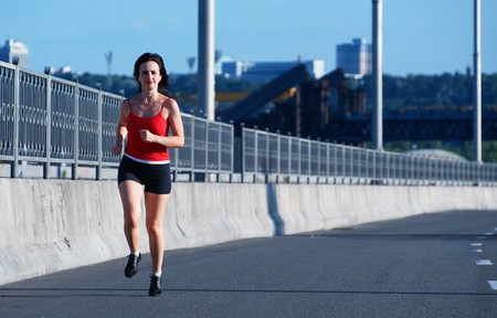 Woman jogging at the highway, front view photo