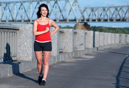 Woman race walking at the embankment Stock Photo