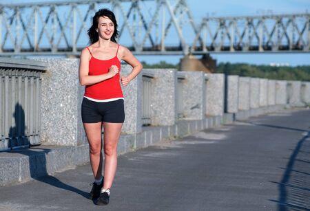 Woman race walking at the embankment Stock Photo