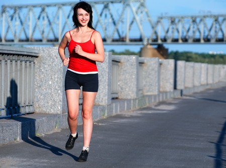 Woman jogging at the embankment in the sunny day Stock Photo - 7390202