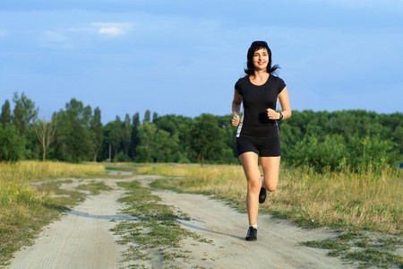 Happy woman jogging outdoors in summer
