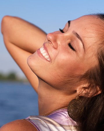 Beautiful girl with closed eyes at the river shore photo