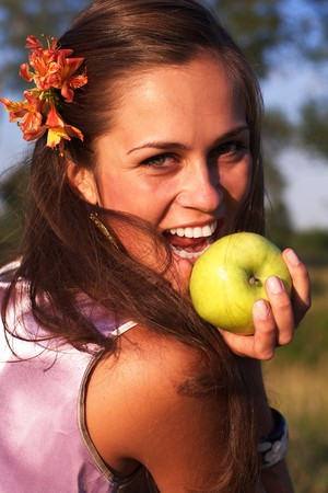 Beautiful woman with apple with flower in hair photo