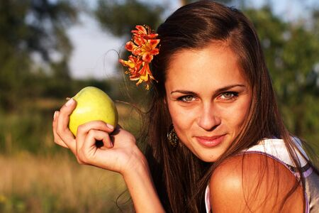Beautiful woman holding green apple with flower in hair Stock Photo - 7447642