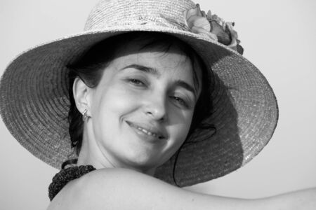 Grayscale portrait of woman in straw hat on the beach photo