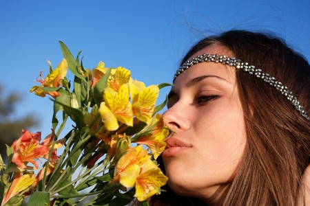 Hippie girl smells lily on the blue sky background photo