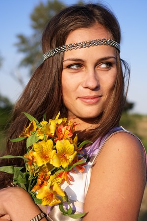 Hippie girl with lily outdoors in summer photo