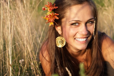 Beautiful smiling girl with flower in hair on the grass photo