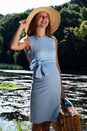 Pregnant woman in blue dress and straw hat on the river with suitcase