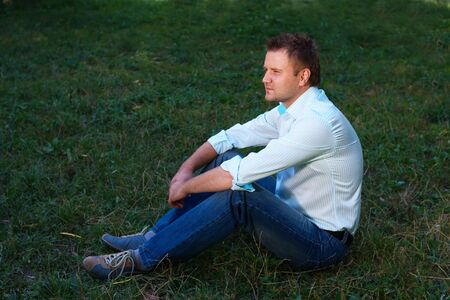 Young man sitting on the grass on summer meadow