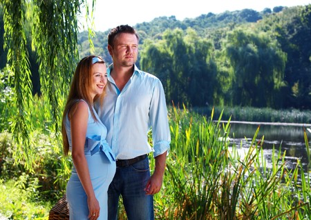 Loving couple standing on the river shore looking forward photo