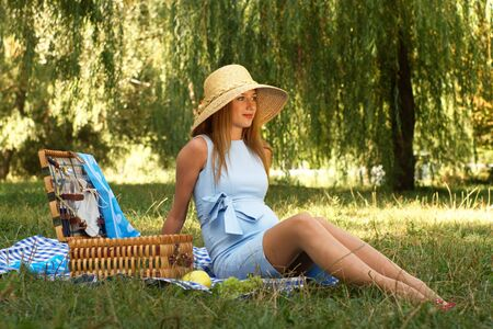 Pregnant woman sitting on the meadow in straw hat and blue dress Stock Photo