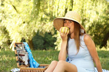 Woman in straw hat bite apple on the summer meadow Reklamní fotografie - 7850081