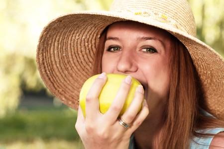 Naughty girl in straw hat bites the apple Stock Photo - 7850079