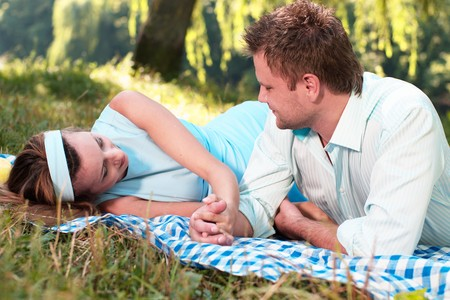 Loving couple in park lie on the carpet holding hands Stock Photo - 7850077