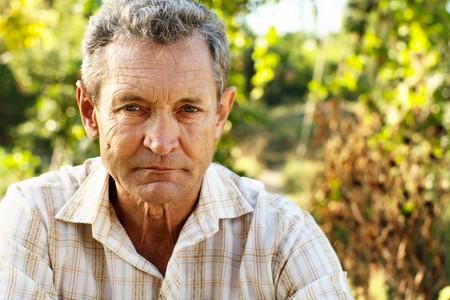 Pensive old man outdoors in summer garden