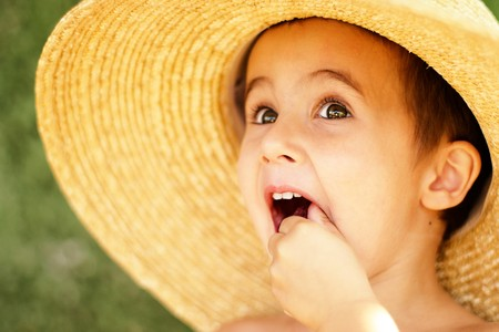 Naghty little boy in straw hat with hude brim outdoors eats raspberry photo