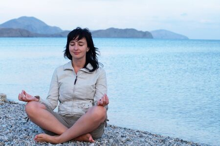 single woman: Single woman sitting on the empty beach relaxing Stock Photo