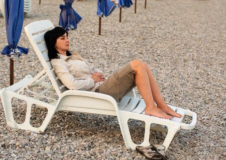 closing time: Woman lie in chaise longue on the stone beach in the evening Stock Photo