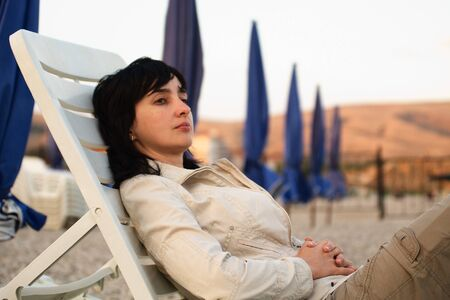 Woman lie in chaise longue on the stone beach in the evening photo