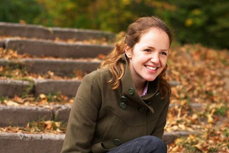 Smiling redhead girl relaxing in autumn forest on the stairs photo