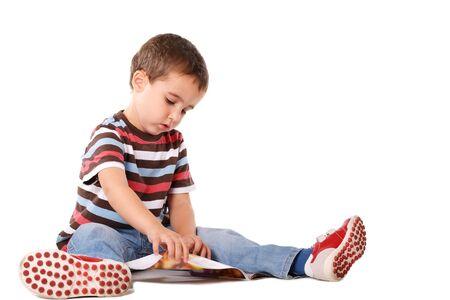 Boy sitting on the floor reading magazine isolated on white photo