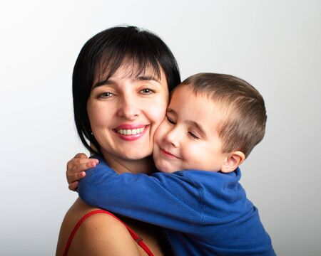 Portrait of mother and son embrace on grey gradien background