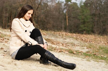 Woman sitting alone on the autumn sand beach photo