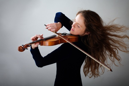Beautiful violinist redhead woman on gray gradient background