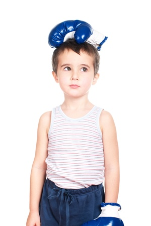 Little boy in tank top with boxing glove on his head isolated on white photo