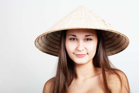Portrait of girl with naked shoulders in vietnamese hat
