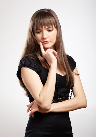 Pensive young woman in black dress photo