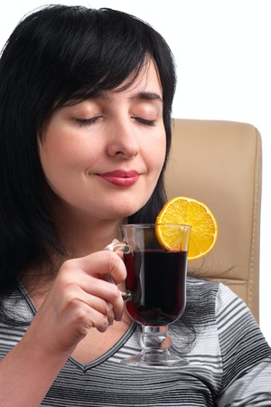 Brunette woman smells mulled wine with orange slice sitting in leather chair isolated on white photo