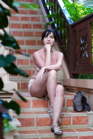 Pensive woman in shorts on the stairway outdoors in summer photo