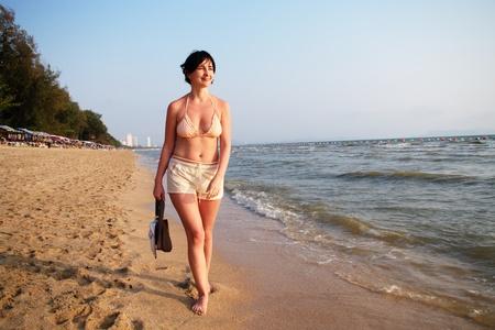 Woman walking on the beach by the sea edge photo