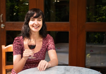 Woman drink glass of red wine on summer cottage veranda photo
