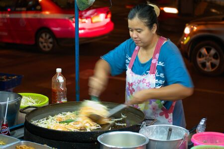BANGKOK - MARCH 03: Street cook woman preparing phat thai noodles in the night, March 02, 2011, Bangkok, Thailand