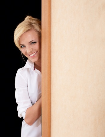 Beautiful blonde woman in white blouse looks out of the doorway Stock Photo - 9180656