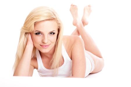 Belle femme blonde en blanc débardeur et pantalon mentir aux pieds nus Banque d'images - 9180640