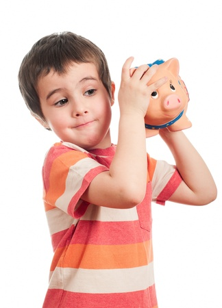 find out: Little boy shaking the piggy bank to find out the contents isolated on white