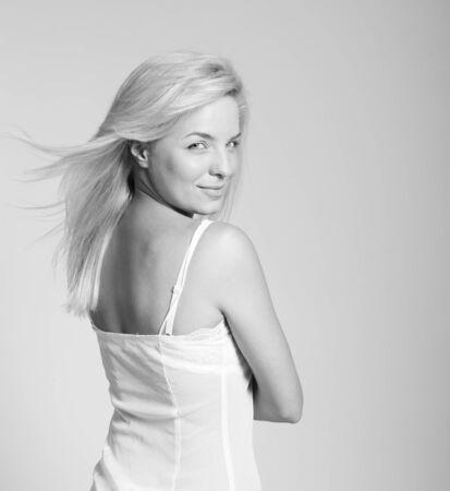 Portrait of beautiful blonde woman in slip embracing herself