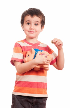 litle: Litle boy puts the coin into the piggy bank isolated on white Stock Photo