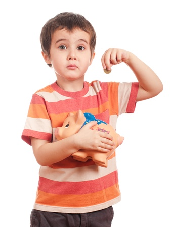 Sad litle boy puts the coin into the piggy bank isolated on white