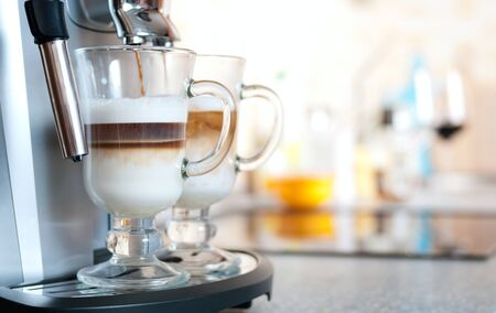 Glasses fileed with capuccino in cofee machine on kitchen