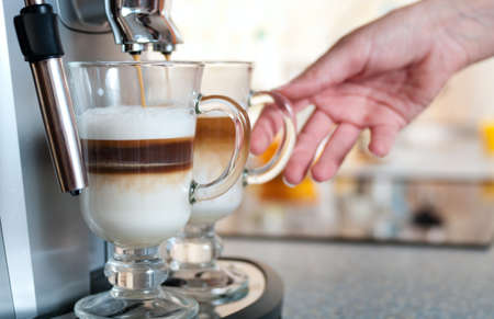 Glasses fileed with capuccino in cofee machine with womans hand on kitchen  photo